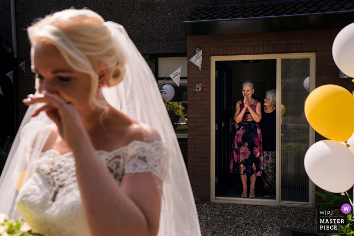 The mother, standing in the doorway is so happy to see her daughter, who is emotional on her wedding day in the Netherlands