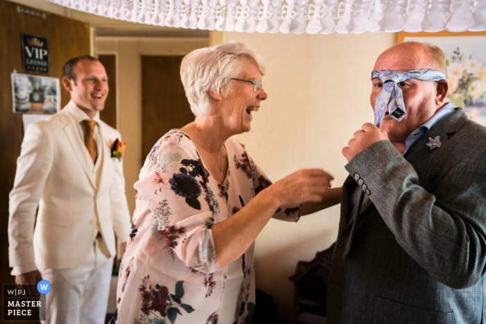 """Netherlands wedding photographer """"putting on a tie isn't that easy and the mother of the groom is having a laugh about the scenario"""""""