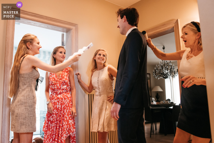 The bride's mom and the sisters of the bride are prepping the groom before his wedding ceremony