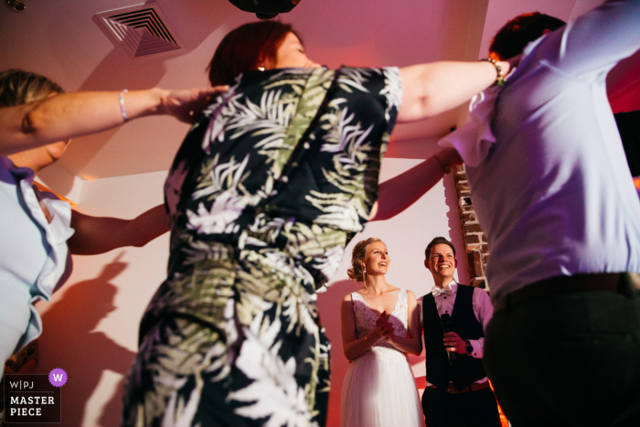 Belgium bride and groom watch their guests perform a surprise act during their evening speech