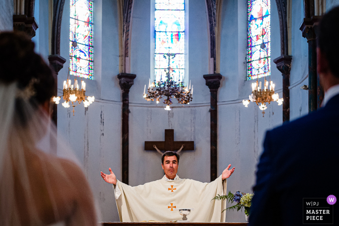 Priest during Mass with arms out of his head for this French wedding ceremony