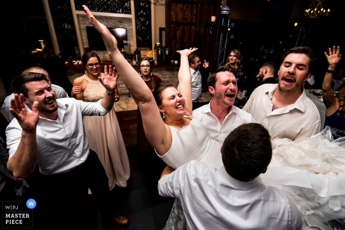 Bride being lifted into the air during dance party at the Pinery at the Hill (Colorado Springs, CO)