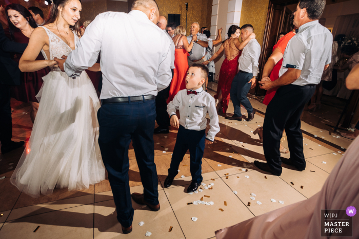 The boy tries to ask the bride to dance at the Hotel Corona Palace, Leznica Wielka, Poland