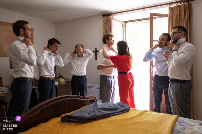 The groom with his groomsmen all put on their ties in preparation for the wedding ceremony