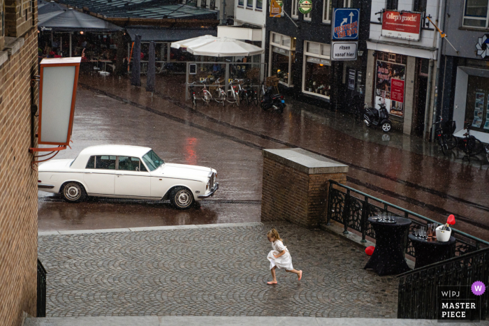 Flowergirl running to shelter from the rain in Hengelo in Overijssel