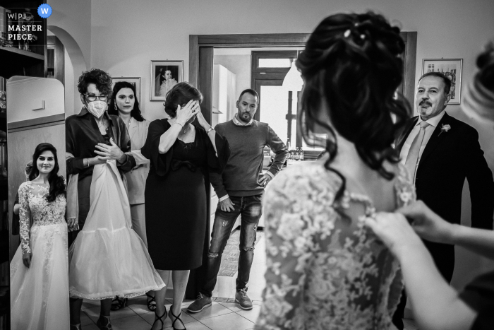 Mother of the Bride and guests facing just dressed Bride in Italy