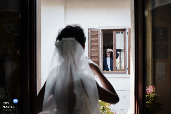The grandfather greets his granddaughter from the window across the street in Varese, Italy