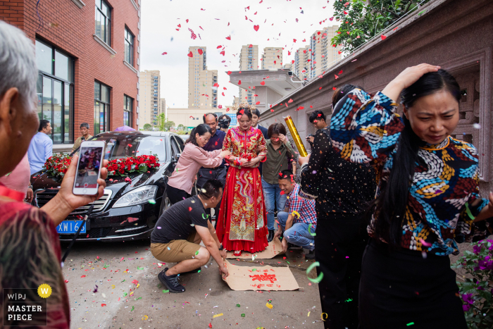 Chinese wedding image: In local wedding customs, the bride must step on the cloth on the ground to enter the bridegroom's door