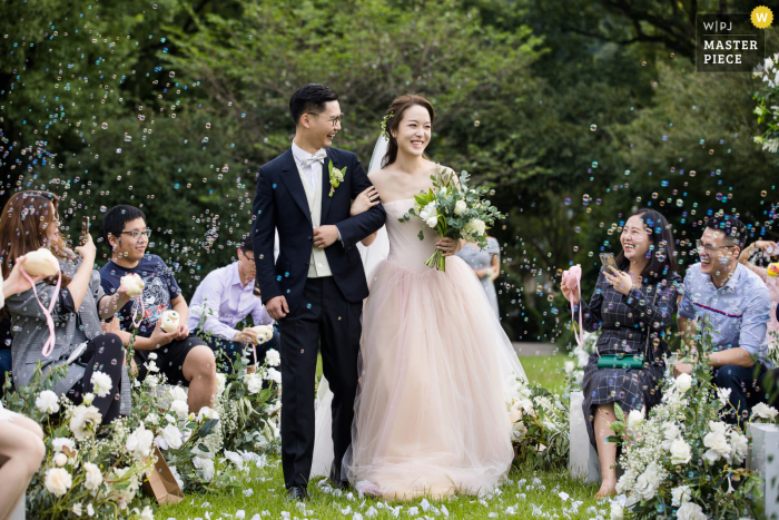 Bride and groom exit their outdoor ceremony with guests blowing bubbles