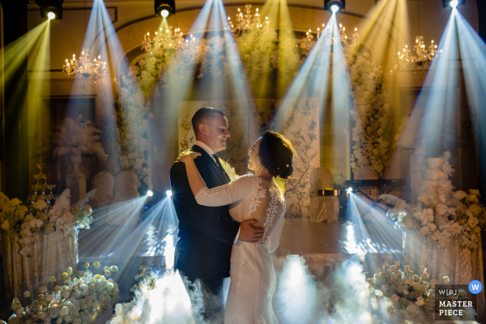 Bride and groom dance with an array of spotlights hitting the dancefloor