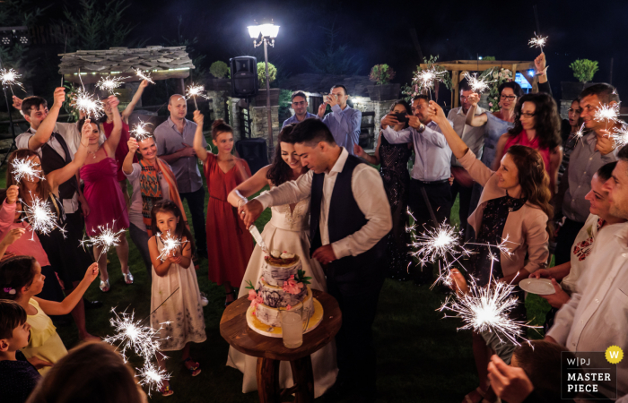 The bride and groom, surrounded by wedding guests, cut their cake at Glavatarksy Han Residence in Bulgaria