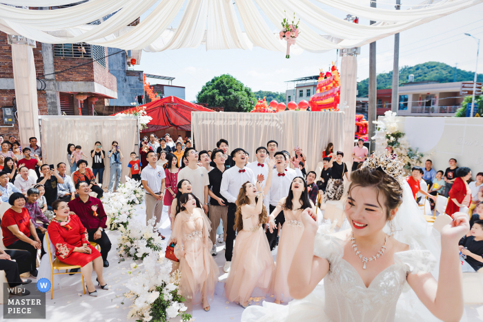 Quanzhou Fujian wedding photography of the bride tossing her bouquet of flowers to guests at home