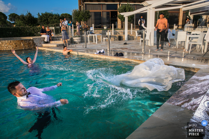 Wedding photo from Serra De 'Conti showing the bride having Fun in the water of the pool