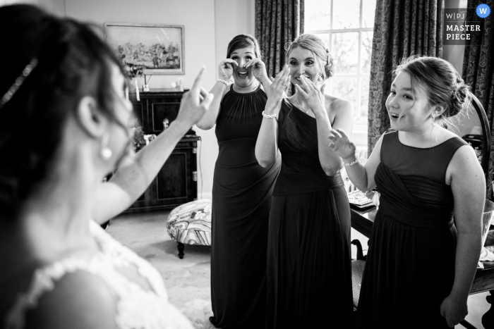 Bridal party reacts as they see the bride in her wedding dress at Iscoyd Park, UK