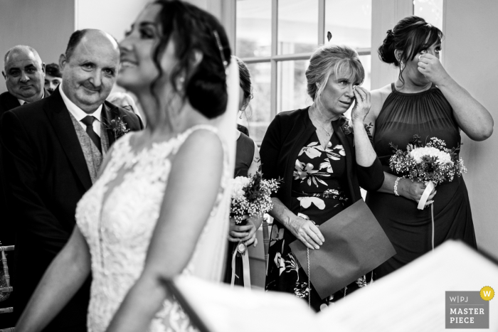 Black and white image of the Mother of the bride and bridesmaid wiping away tears during ceremony at Iscoyd Park in the UK