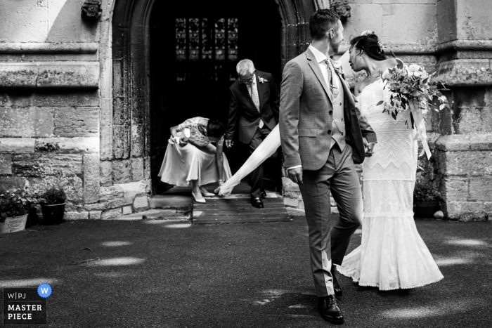 The veil catches as the bride and groom leave the St Mary Magdalene Church in Brampton, UK