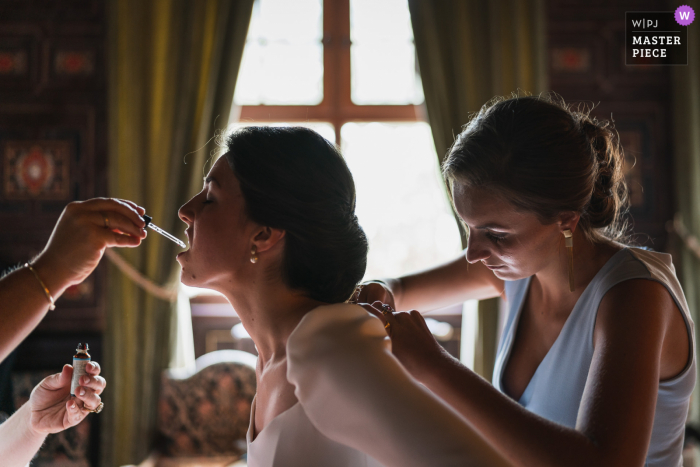 Bride receives help with her dress and lipstick before her Brissac-Quincé, France wedding