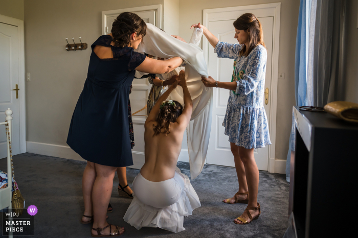 Bride is getting some help putting on her wedding gown for her France ceremony