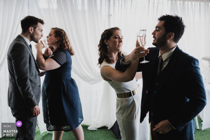 The newlyweds interlock arms as they drink their champagne after their ceremony, mirrored by their witnesses (also husband and wife), who are doing the same thing at The Merchant Hotel in Belfast