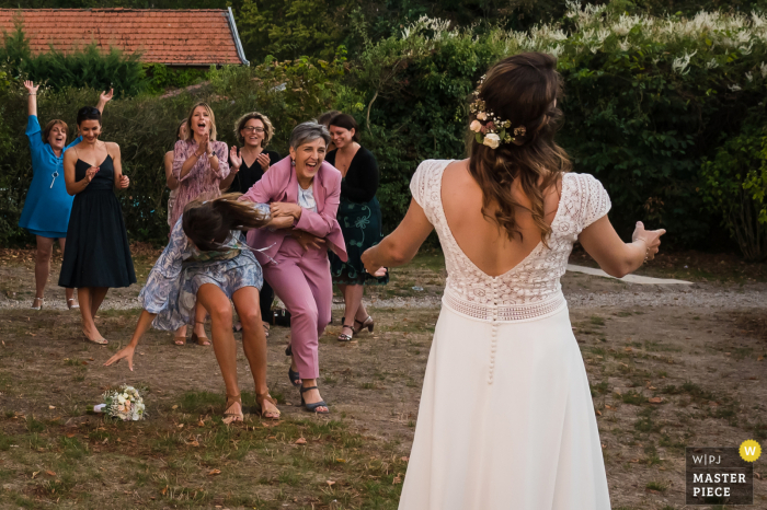 Wedding photography from a Auvergne-Rhône-Alpes Reception Venue of women guests fighting over the brides bouquet when tossed