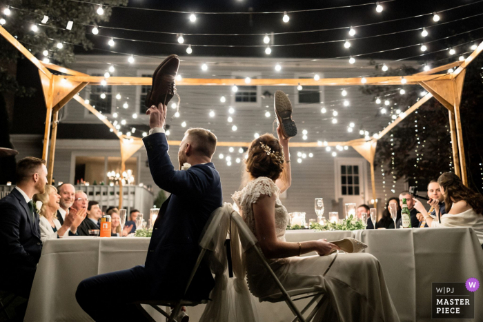 A bride and groom playing shoe game at their wedding reception in Boston, MA