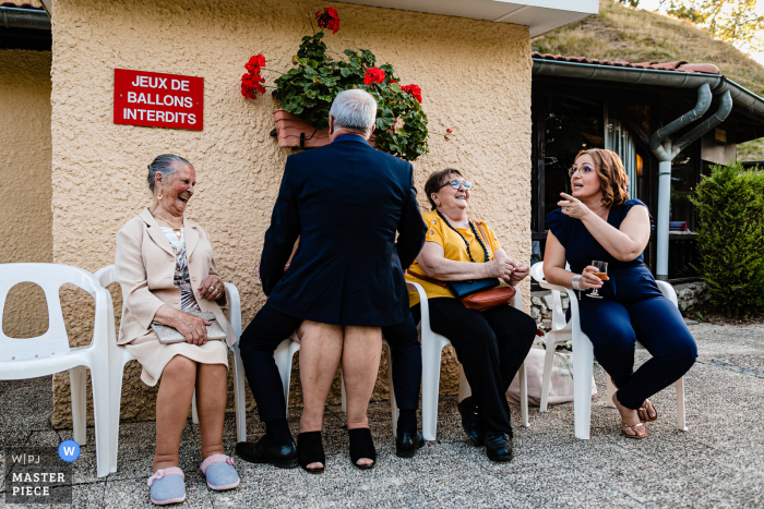 The father of the groom sits on his wife's lap during this French wedding reception