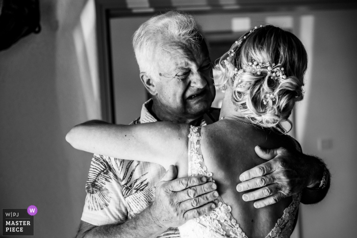 French bride hugs her emotional father on one of the biggest days of her life