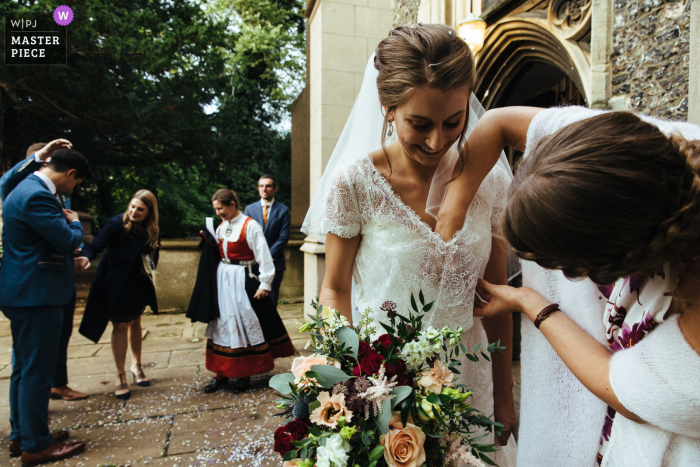 bridesmaid removes confetti from bride's dress at the Streatham Church