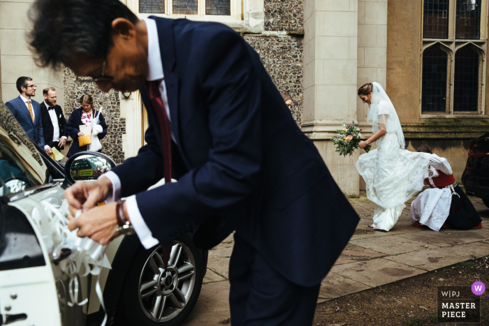 England wedding photography from outside Streatham church of the bridal car getting decorated
