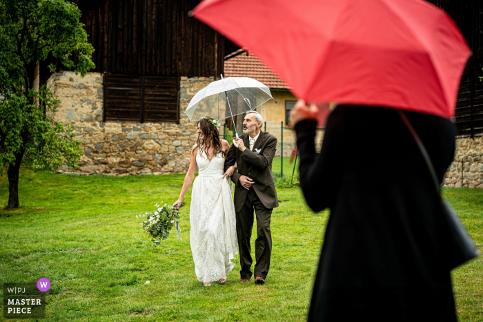 The bride and her father walk to the ceremony while carrying an umbrella to shield from the rain in Samota Křemen