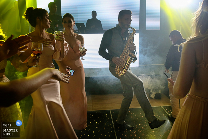 Smoky image of the saxophonist playing during a wedding reception at the Villa Borguese Anápolis