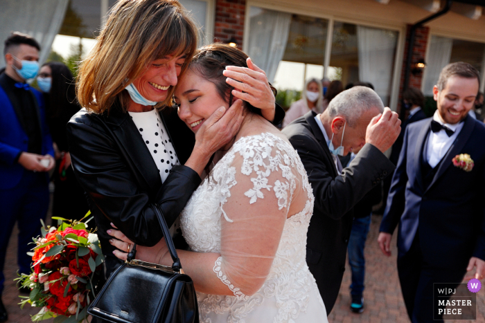 immediately after the launch of the rice, the bride and her mother hug each other excitedly at the Antica Cascina Margherita in Barbania, Torino, Italy
