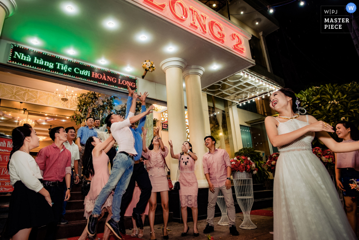 Vietnam Ceremony Location wedding photography of the bride tossing her bouquet outdoors at night