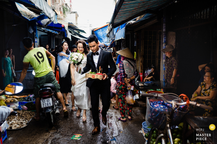 Ho Chi Minh wedding photography of the bride and groom walking through a crowded street market