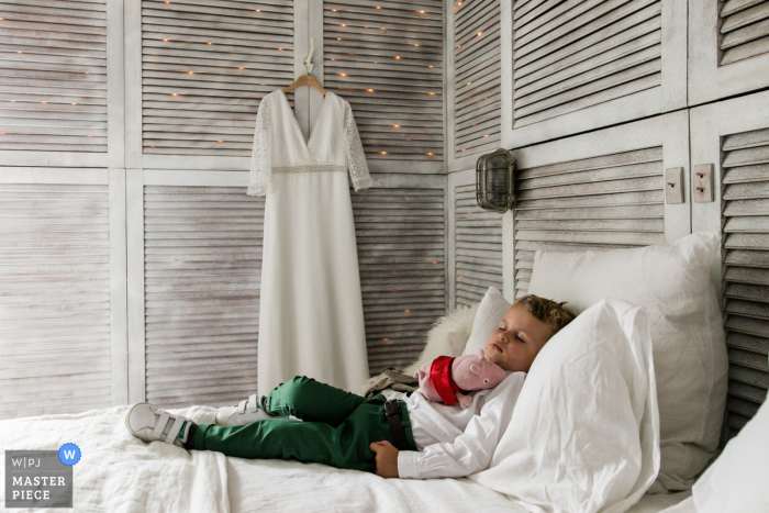 France wedding photography of a child taking a nap next to the brides hanging dress
