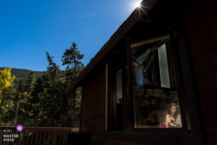Small wedding photography from a Colorado Private Home event of the Bride getting ready in a lit window frame