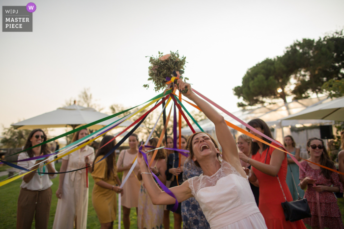 Wedding photography from outdoor reception at Reception venue : Villa La Tosca, France of the Bride giving her bouquet