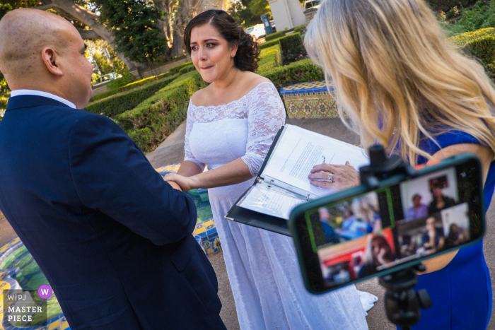 Tears run down on the bride's face during a Balboa Park (San Diego) elopement wedding ceremony while family members watch it via a live-streaming call