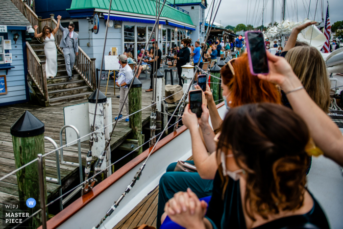 Maryland wedding photographer captures this image of the bride and groom meeting their guests on a ship for cocktail hour