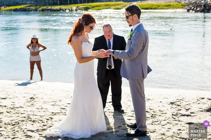 Exchanging rings at your beachside elopement ceremony on a holiday weekend means unexpected guests will be cheering you on from afar in bathing suits at Ogunquit, Maine