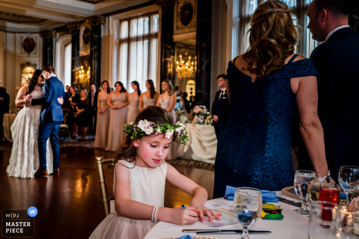 The flower girl colors while the bride and groom do their first dance at The Belvedere in Baltimore, Maryland