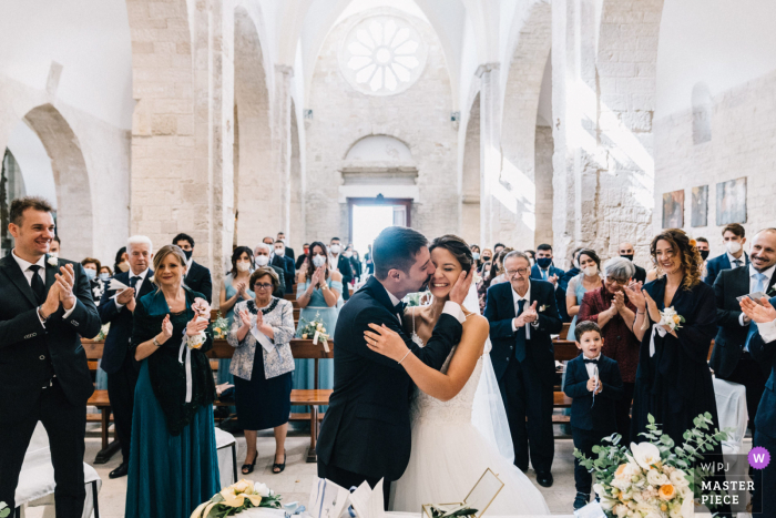 Puglia church ceremony image of the groom kissing his bride
