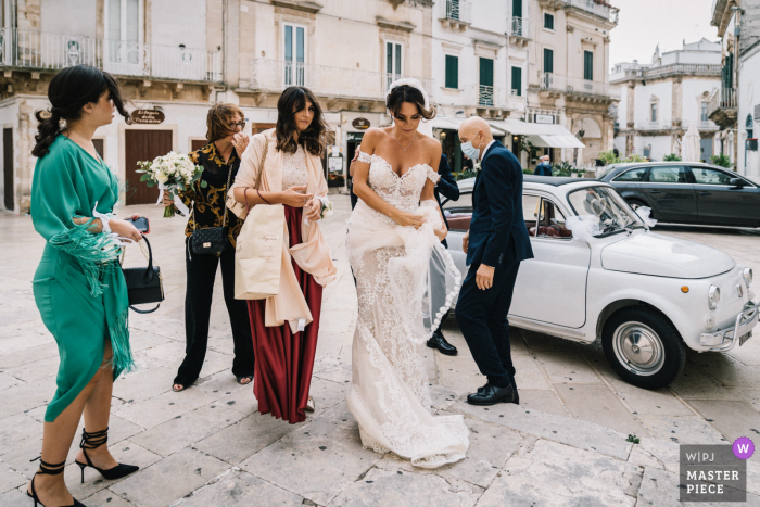 Puglia bride and lady attendants arriving while being hit by high winds