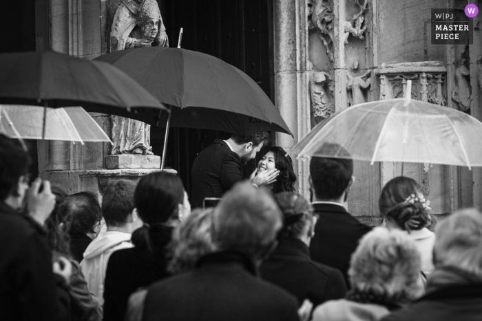 French wedding photographer made this image in Serans of the bride and groom surrounded by guests with umbrellas