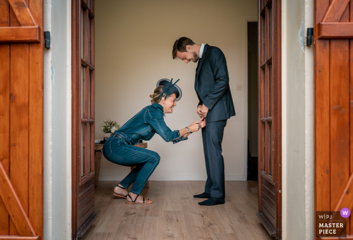 """Sister helping out her groom brother during """"getting ready"""" at home in France"""