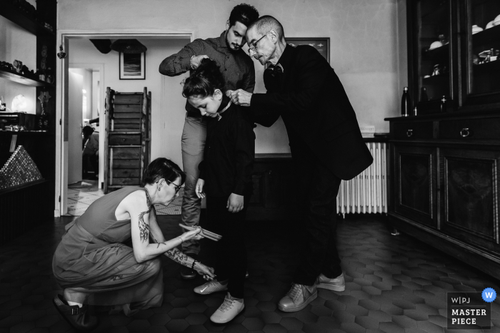 Oradour-sur-Glane wedding picture of a kid getting ready, attended to by three adults