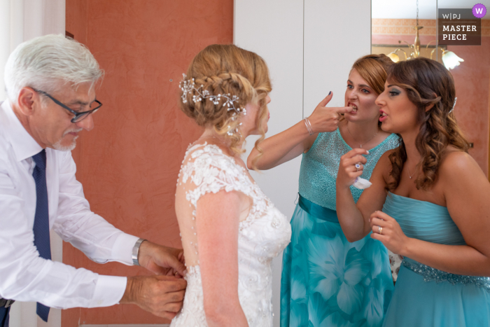 Siracusa bride receives help with her dress from her father and help from bridesmaids with something on her teeth