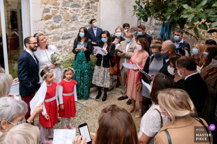 FR wedding photography from the Nimes Town Hall South of France showing All the guests singing a song to the newlyweds