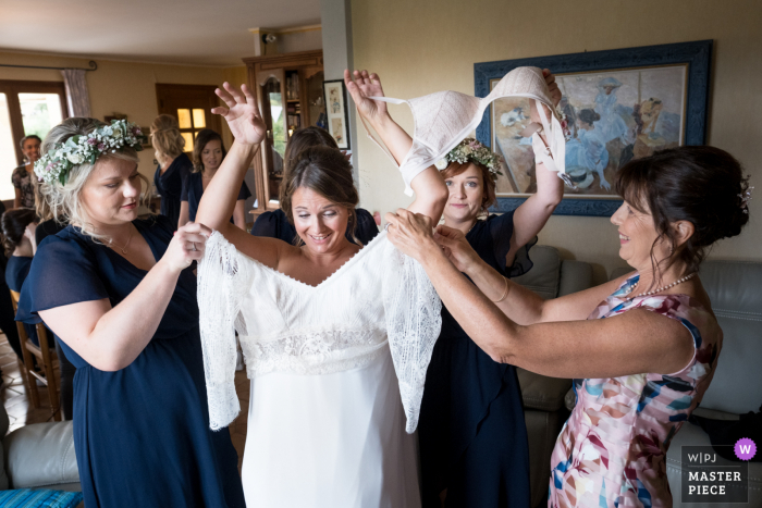 Turenne wedding photo of the bride putting on her gown with family and friends there to help