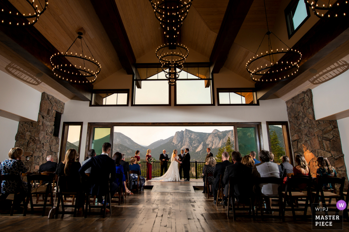 Black Canyon Inn Estes Park, CO wedding photography using a wide shot of the indoor wedding ceremony